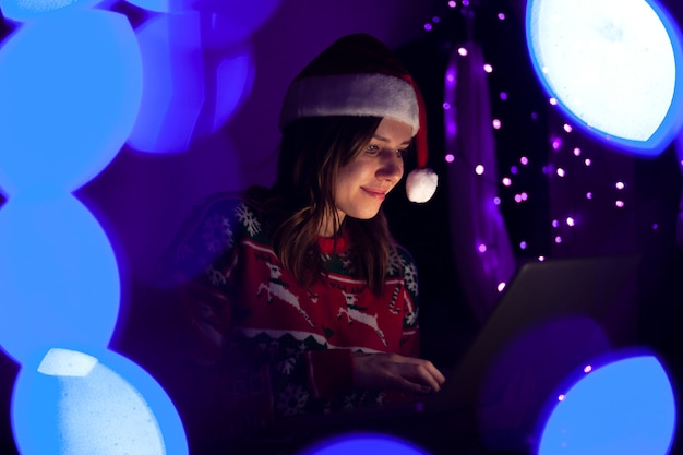 Girl student in christmas clothes sits at home with a laptop at night