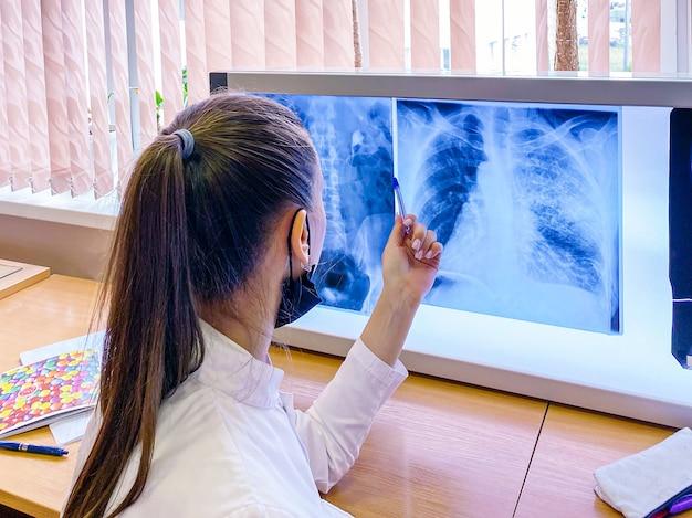 女子学生が大学の臨床検査室でレントゲンを調べる