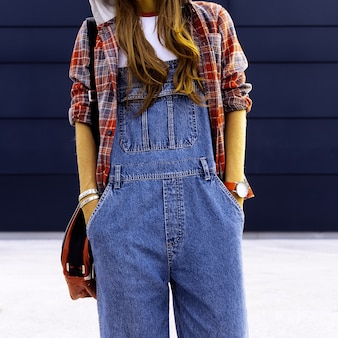 Girl student. in fashionable denim overalls. urban style