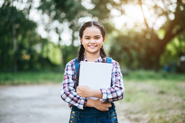 Girl student hand hug book