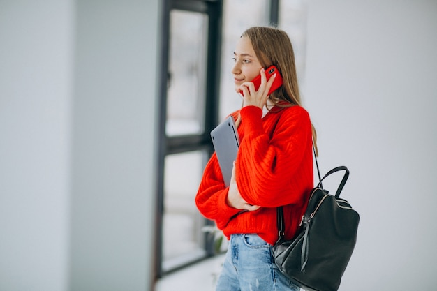 여자 학생 컴퓨터를 들고 창에 의해 전화 통화