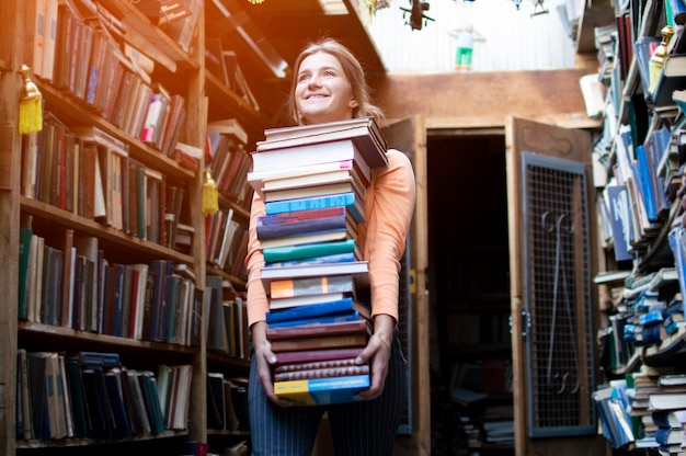 女子学生は本の大きなスタックを保持し、図書館で多くの文学を運ぶ、彼女は勉強の準備をしています、本の売り手は本屋を背景に多くの本を取りました