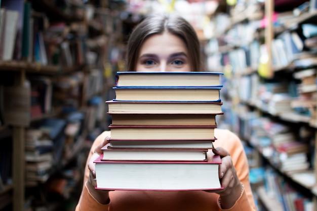 女子学生は図書館で本の束を保持し、彼女は文献を検索して読むことを申し出ます、女性は勉強の準備をします、知識は力です、書店の書店