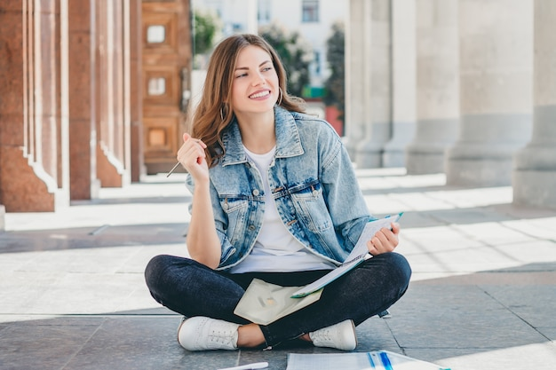 Girl student sits opposite the university and smiling. cute girl student holds pensil, folders, notebooks and laughs. girl teaches lessons