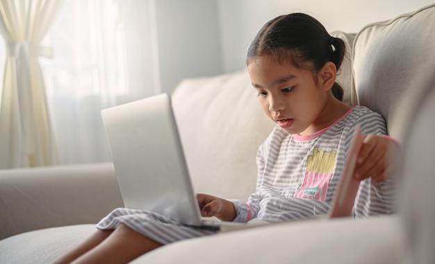 여자 학생 테이블에 앉아 숙제를 작성합니다. 노트북 컴퓨터를 사용하여 공부하는 십대. 새로운 정상 사회.