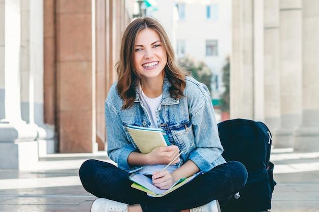 女子学生が大学の近くに座って、笑顔します。かわいい女子学生がフォルダー、ノートブックを保持し、笑う