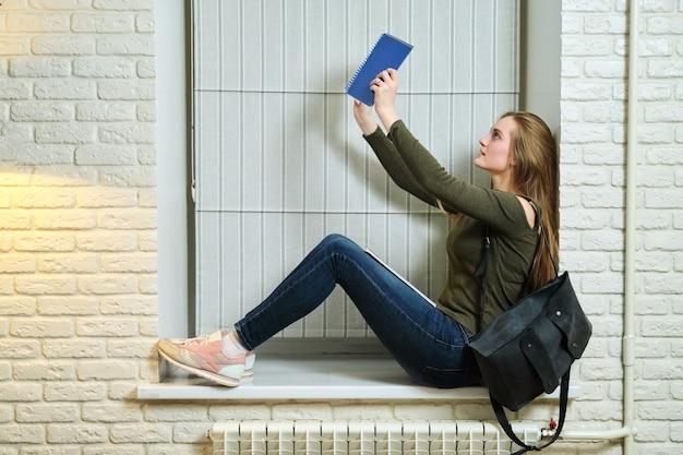 여자 학생 창턱에 앉아 공부, 노트북을 읽고