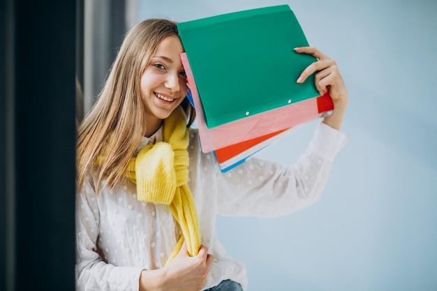 다채로운 폴더와 함께 서있는 여자 학생