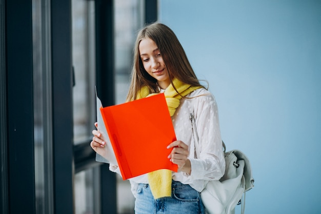 Girl student standing with colorful folders