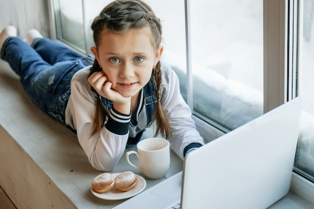 Girl student study online with video call teacher at laptop at home and drink tea and eat cookies