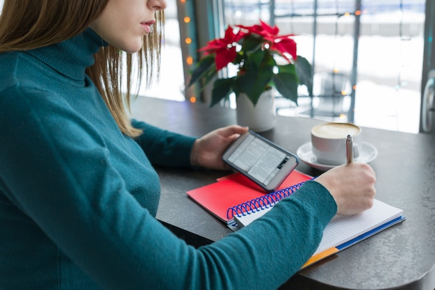 Girl student studying in cafe using smartphone and notebook