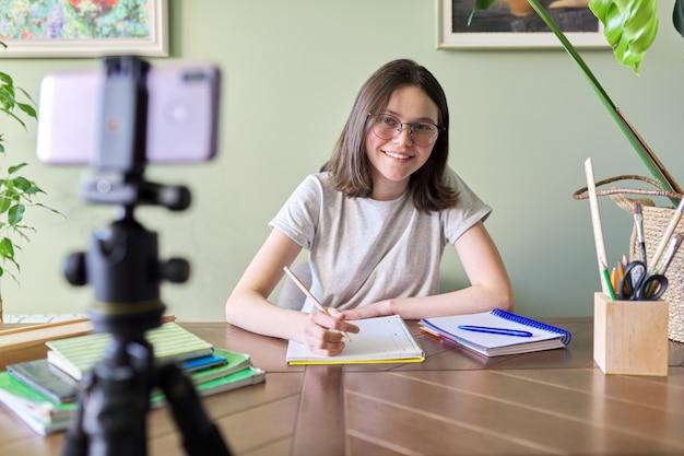 Девушка-студент подросток учится онлайн с помощью смартфона, видеоконференцсвязи, видеозвонка, дистанционного обучения, обучения дома