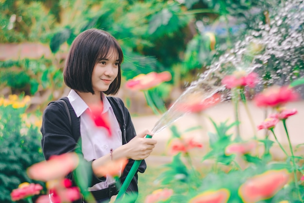 Girl student watering flower in the garden