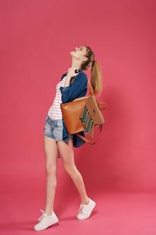 ピンクの背景のポーズをとってファッション服バックパックを身に着けている女子学生
