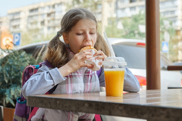 Girl student with backpack, eating burger with orange juice