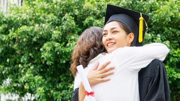 卒業式のガウンと帽子を持つ女子学生は、お祝いの式典で親を抱擁します。