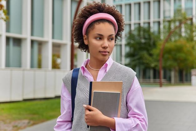 大学で勉強している女の子は大学に行き、2つのメモ帳を持ってカジュアルな服を着た物思いにふける表情で目をそらし、外の都市の建物に対してポーズをとる