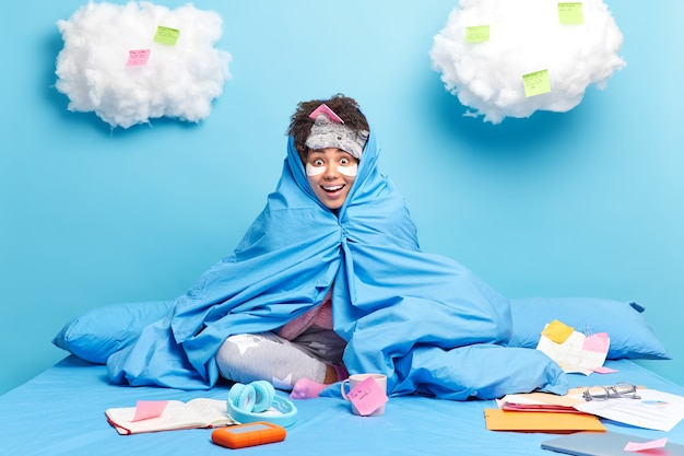 Girl studies remotely from home during quarantine wrapped in blanet makes mlist to do on sticky notes looks happily isolated on blue wall