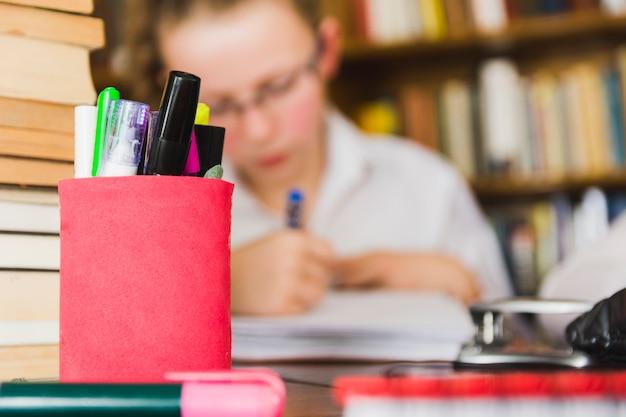Девушка учится у стола с канцелярскими принадлежностями