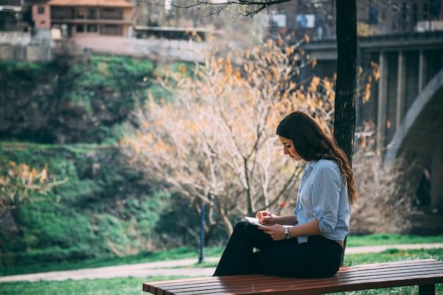 Девушка учится в парке