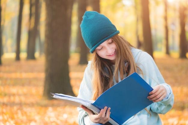 秋の公園で勉強している女の子