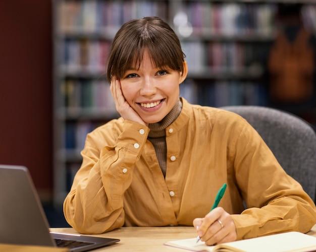 Девушка учится в университетской библиотеке