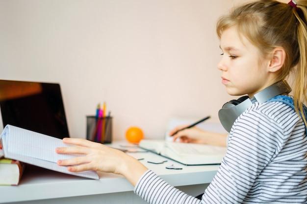집에서 컴퓨터와 헤드폰을 사용하여 무언가를 공부하는 소녀