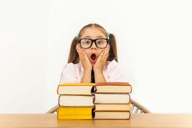 Girl studying at table on white background