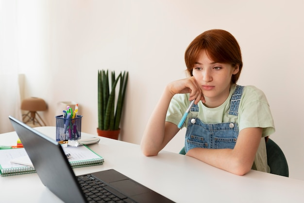 Девушка учится с ноутбуком дома средний план
