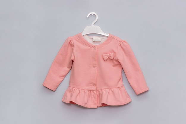 Girl styled look. pastel pink elegant jacket on hanger. female children's fashion clothes concept