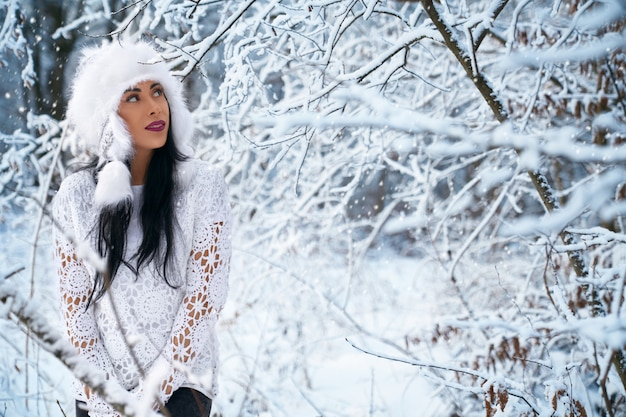 Girl in stylish warm hat, knitted blouse in winter forest.