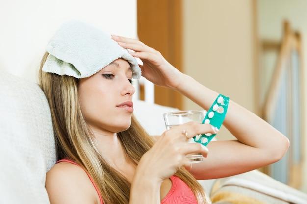頭痛から苦しんでいる少女は、丸薬を取る