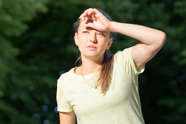 痛み、熱、熱射病の女性に苦しんでいる女の子。夏の暑い時期に日射病を患う。危険な太陽、太陽の下の女の子。頭痛、気分が悪い。人は頭に手をかざします。コロナウイルス