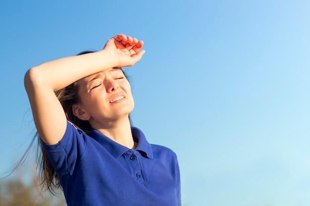 열사병으로 고통, 열, 여자로 고통받는 소녀. 여름 더운 날씨에 일사병을 겪고 있습니다. 위험한 태양, 햇빛 아래 소녀. 두통, 기분이 나쁘다. 사람은 머리에 손을 보유하고있다.