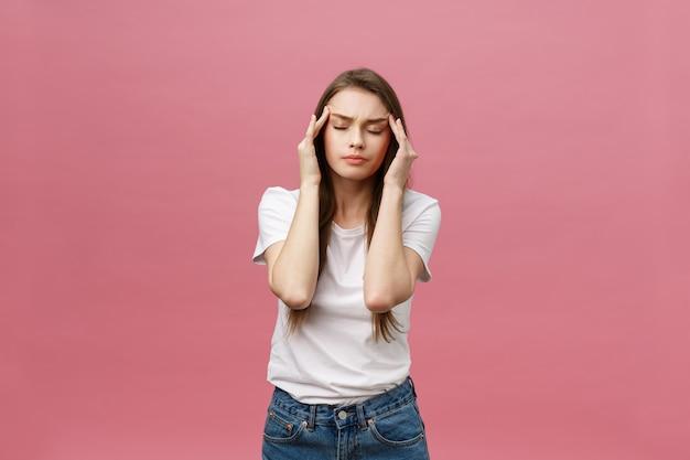 Девушка страдает от ужасных головных болей и сжимает голову пальцами
