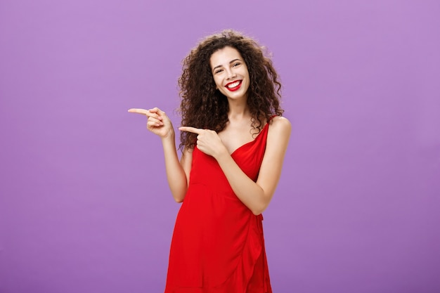 Girl suggesting copy space to try. portrait of good-looking elegant caucasian woman with curly hair in stylish evening red dress pointing left and smiling inviting customers over purple background.