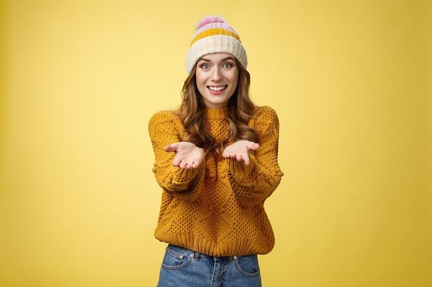カメラに向かって広く友好的な腕を伸ばして笑顔で心を奪うことを提案している女の子は、明るい気持ちで笑顔で喜んでいるのを助けたい友人に感謝したい努力、黄色い壁に感謝したい