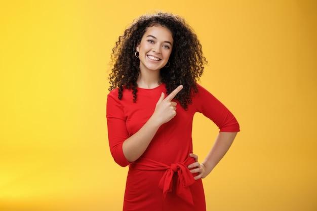 新製品を試してみることを提案している女の子。フレンドリーで楽しい幸せな若いヨーロッパのブルネットは、巻き毛が頭を傾けてかわいい、広く笑って、右上隅を指して広告を指示します。