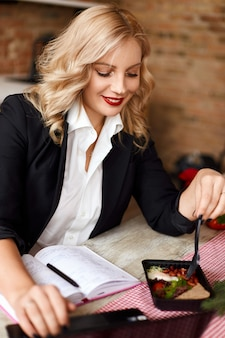 A girl in a suit has lunch and makes notes in a notebook. food delivery