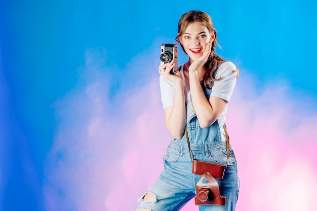 Girl on a suitcase with a camera on a blue background going on vacation, tourism concept