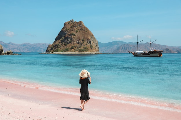 A girl in summer hat walking on pink sandy beach enjoying the view of  ship sea with hills