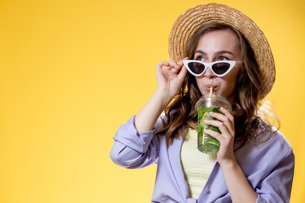 Girl in summer outfit wearing white trendy sunglasses and enjoying while drinking a mojito cocktail. posing on the yellow background.