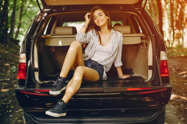 Girl in a summer park near car