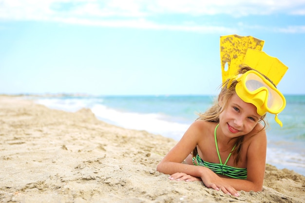 Girl sunbathing on beach in mask and fins for scuba diving.