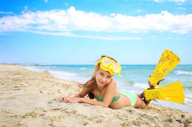 Девушка загорает на пляже в маске и ластах для подводного плавания.