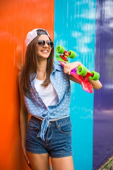 Girl in sunglasses and cap standing against colorful wall.