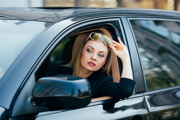 La ragazza in occhiali da sole guida una macchina e guarda dalla finestra