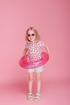 Ragazza in occhiali da sole e un cerchio gonfiabile dell'acqua su una superficie rosa