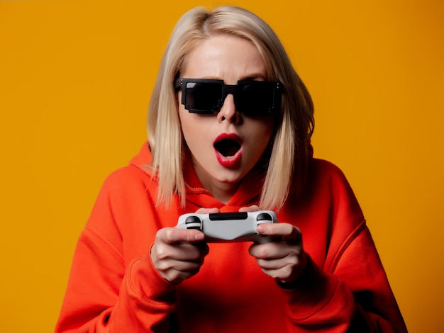 Girl in sunglasses plays with a joystick