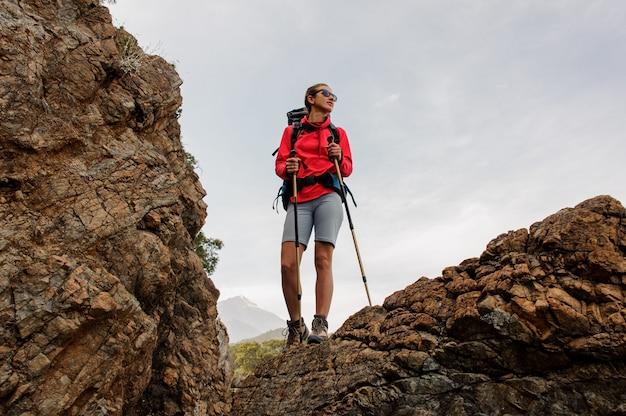 Girl in sunglasses standing on the rock with hiking backpack and walking sticks